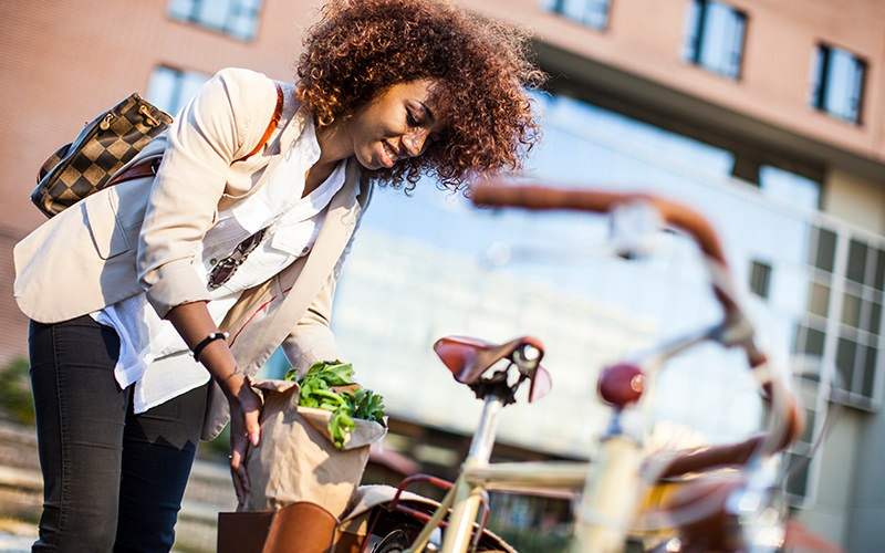 A woman loading flowers into her bike.