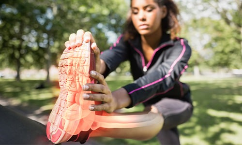 A jogger is stretching her leg before a run.