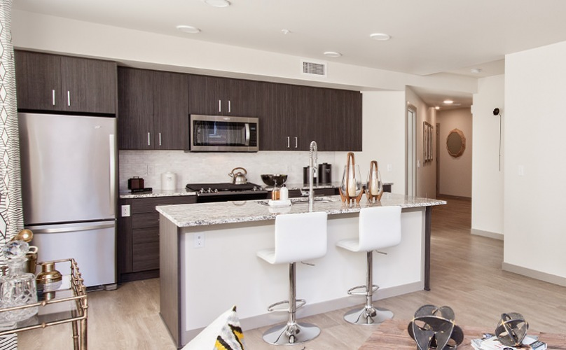 Spacious kitchen with wood floors and access to the dining area and living room.