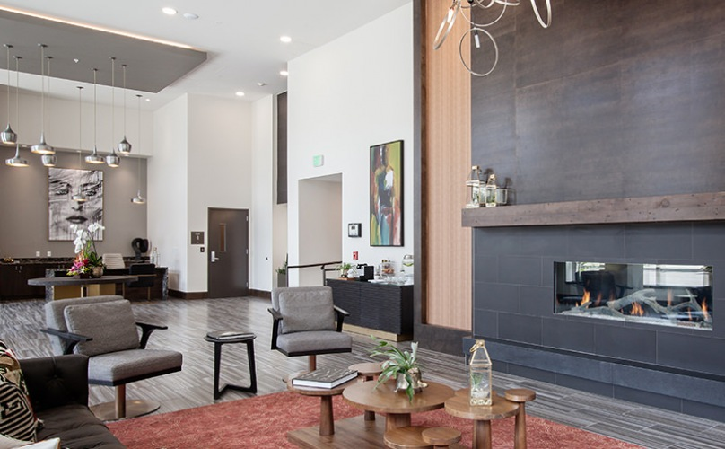 Spacious and well lit lobby with plenty of seating and large windows with a view of the city